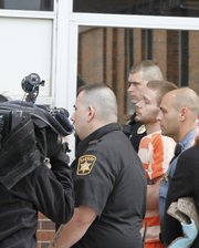 Kyle T. Flack, 27, is transported from the Franklin County courthouse Friday after being charged with four counts of murder and one count of rape. Flack is being held on a $10 million bond.