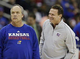 Kansas coach Bill Self, right, peeks around assistant coach Doc Sadler during practice for a second-round game in the NCAA basketball tournament at the Sprint Center in Kansas City, Mo., Thursday, March 21, 2013. Kansas is scheduled to play Western Kentucky on Friday.