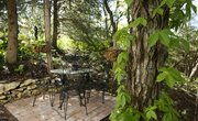 The Bogards have incorporated a small patio area within a natural wooded space along the side of their home.