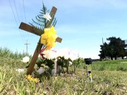 A cross, flowers and a picture of 18-month-old  Lana-Leigh Bailey, whose body was found Saturday evening in Osage County, sit at the intersection of Georgia and Highway 68 In Ottawa Monday. Police say they believe Lana-Leigh was killed, along with her mother and two other men, at a farmstead at 3197 Georgia Road.
