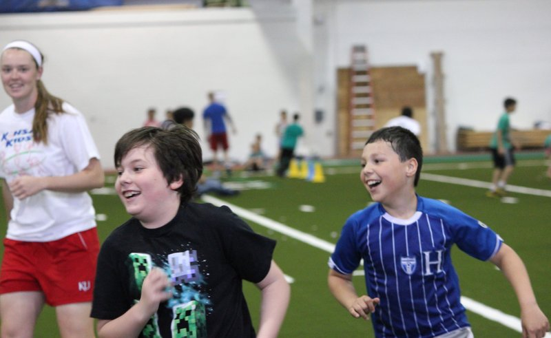 Students race to a new spot in Freeze Tag as one of the Kansas Kids Fitness Day KU student volunteers looks on.