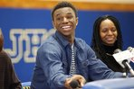 Huntington Prep basketball player Andrew Wiggins smiles along side his mother Marita Payne-Wiggins, right, as he announces his commitment to Kansas University during a ceremony on Tuesday, May 14, 2013, at St. Joseph High School in Huntington W.Va. The Canadian star, a top prospect, averaged 23.4 points and 11.2 rebounds per game this season for West Virginia&#39;s Huntington Prep.