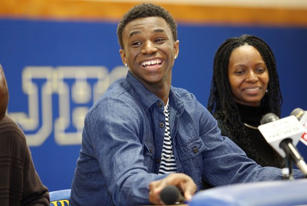 Huntington Prep basketball player Andrew Wiggins smiles along side his mother Marita Payne-Wiggins, right, as he announces his commitment to Kansas University during a ceremony on Tuesday, May 14, 2013, at St. Joseph High School in Huntington W.Va. The Canadian star, a top prospect, averaged 23.4 points and 11.2 rebounds per game this season for West Virginia's Huntington Prep.