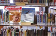 Five-year-old Taylor Brown browses the shelves of kids' books at the Lawrence Public Library's temporary location in the old Borders building at Seventh and New Hampshire streets earlier this month.