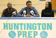Huntington Prep basketball player Andrew Wiggins, center, flanked by his parents Mitchell Wiggins and Marita Payne-Wiggins, as he announces his commitment to the University of Kansas during a ceremony, Tuesday, May 14, 2013, at St. Joseph High School in Huntington W.Va. The Canadian star, a top prospect, averaged 23.4 points and 11.2 rebounds per game this season for West Virginia's Huntington Prep.