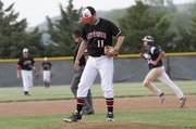 Lawrence High pitcher Brandon Bell (11) swipes the mound with his foot as Manhattan runner Jacob Priddle (24) rounds the bases after a two-run home run in the bottom of the first of a Class 6A regional final on Wednesday, May 15, 2013, in Manhattan.