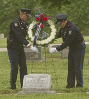 Officer Vince Casagrande, left, and Detective Randy Glidewell place a wreath on the grave of Officer Allen Moore at Maple Grove Cemetery. Moore, who died in 1901, was one of three Lawrence police officers who have died in the line of duty and are honored during National Police Week.
