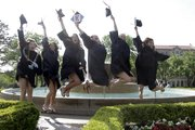 Chi Omega sorority members jump in front of the Chi Omega fountain for family members during commencement ceremonies Sunday, May 19, 2013.