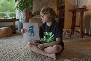 Matt Reimer, 9, holds a color print of one of the imaginary creatures he's drawn to inhabit a make-believe planet he calls Matthewland. Prints of Matt's creatures will be for sale along with national and local artists' work at an upcoming event hoped to raise money to research a cure for Matt and other boys with a rare genetic disorder called X-linked adrenoleukodystrophy.