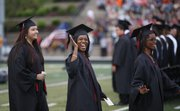 Lawrence High graduate Octavia Kelly waves to her family members in the crowd as she and her sister, Nakia Kelly, right, proceed to take their seats for the 2013 commencement ceremony on Tuesday, May 21, 2013 at Lawrence High School. Nick Krug/Journal-World Photo