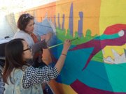 Lawrence native Vanessa Vanek, left, who teaches art at Chadwick International School in Songdo, South Korea, paints alongside a student. Vanek, her students and Lawrence mural artist David Loewenstein collaborated to create the first mural in Songdo Central Park.