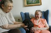 Fay Jost, right, who on Monday will turn 105 years old, visits with her longtime friend Doreen Zimmerman and her dog Tippie on Friday in Jost's apartment at Vermont Towers.