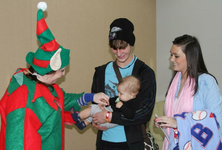 Mandy Gwirtz, left, visits with 5-month-old Ashton Walker and his parents, Zach Walker and Emily Rader during a holiday party at the Lawrence-Douglas County Health Department.