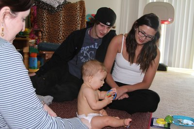 Mandy Gwirtz, Healthy Families Douglas County case manager, left, watches how 6-month-old Ashton Walker grasps his toys along with his parents Zach Walker and Emily Rader during a home visit in January 2013. Mandy is looking at Ashton's motor development skills.