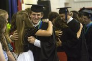 "Richard Gwin/Journal World Photo. Michael Kressig gives a hug to a junior as other grads follow during the ""Stepping Up"" ceremony during Bishop Seabury&squot;s 2013 graduation ceremony on Friday May 24, 2013."