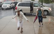 Lacey Greenfield, 13, left, and her grandmother Carol Greenfield, run through a heavy rain into the Dorsey-Liberty Post No. 14 American Legion Hall, 3408 W. Sixth St., on Monday before Memorial Day services. Heavy morning rains cancelled outdoor ceremonies at the veterans plot at Oak Hill Cemetery.