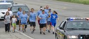 Sharing the torch as they head south on U.S. Highway 59, Douglas County Special Olympians Brady Tanner and Becky Saathoff participate in the start of the annual Law Enforcement Torch Run from Lawrence to Ottawa on Tuesday. The run benefits Special Olympics, and the Lawrence to Ottawa leg featured several officers from both the Lawrence Police Department and the Douglas County Sheriff's Office.