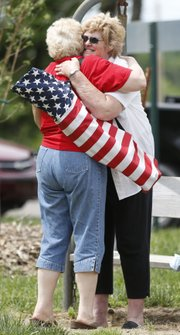 Cousins LaVon Harris, of Pomona, is hugged by Sarah Ann Bowman, back, of Boones Mill, Va., as the two reunite during the Hoover Family Reunion on Saturday
