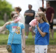 Cousins Carolyn Hoover, 10, of Eudora, left, and Maddie Steele, of Kearney, Neb., keep the conversation short as they bite into their cotton candy during the Hoover Family Reunion on Saturday at Lone Star Lake. The two girls, who had never met before this weekend, are among the almost 180 people from 18 states to converge on Douglas County for the Hoover family's 100th family reunion. Ancestors of the Hoover family settled in Lawrence in 1855.