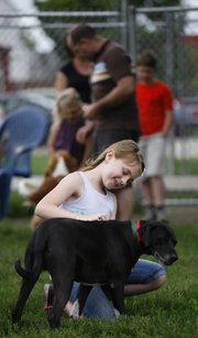 Eight-year-old Lottie Keating pets Tad, a mixed-breed dog, during a meet and greet before adopting him on Saturday at the Lawrence Douglas County Humane Society, 1805 E. 19th St.