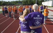 From left, Jeanne Bronoski and John Harrod give each other a hug on Monday at the Free State High School track with volunteers assembled to prepare for this years Relay For Life. Bronoski and Harrod are both cancer survivors. This year's Relay for Life begins Friday evening at the Free State track