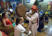 "Shaman Ngema ""Maile"" Lama calls on spirits to clear and protect Andy Claypool during a Chinta ceremony at Elevate Ascension, 1407 Massachusetts St. Lama, a shaman who practices an ancient form of spiritual healing with roots in the pre-Buddhist Bon tradition of Tibet, performed the ceremony to clear and protect the space and those who were present."