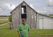Mike Yoder/Journal-World Photo.An old barn, a house and several outbuildings still stand on the farmstead of George Hunsinger's grandfather, who bought the Wakarusa Township property in 1918. Hunsinger, picture in front of the  farmsteads original barn, lives on adjacent property across the road and now rents the house on the property and farms the land.
