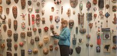 Judy Heller looks over some of the 180 masks on display in the lobby of Theatre Lawrence's new building. The mask collection was given to Theatre Lawrence by Eleanor Woodyard and her late husband, George Woodyard.