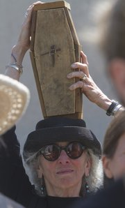 Laurie Ward, of Lawrence, carries a coffin over her head during a mock funeral procession for the state of Kansas.