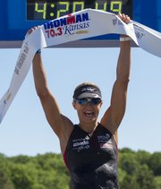 British professional triathlete Emma-Kate Ludbury raises the Ironman banner above her head after winning the professional women's division of the Kansas Ironman triathlon, held Sunday at Clinton Lake State Park.