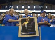 Bruce Bundy, Lawrence, left, and Brian McGee, Gardner, hold up a poster of Olympic gold medalist and Kansas University women's track team member Diamond Dixon as a small crowd gathered inside Allen Fieldhouse on Sunday to welcome home the women's track team.