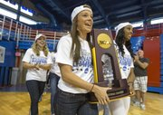 Members of the Kansas University women's track carry the national championship trophy into Allen Fieldhouse in front of a small crowd gathered inside on Sunday to welcome the team home.