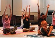Employees at the Lawrence-Douglas County Health Department participate in a yoga session during a recent lunch break.