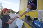 England Porter, Lawrence, right, one of the co-owners of the Blissful Bite food truck, hands Amy Oelschlaeger, Lawrence, an order of quesadillas during the annual Relay for Life event, held Friday, June 7, 2013, at Free State High School.
