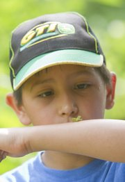 Diego Klish, 9, of Lawrence, checks out an insect on his arm last week at Prairie Park Nature Center during one of the city's summer camps for kids. Parents are using the free time kids have on summer vacation to keep their children active through day camps and classes offered by the city and the Lawrence Arts Center.