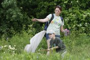 Thomas Alexander-Coffman, 6, tries to scoop up a bug as camp instructor Katrin Gubser helps on a trail at Prairie Park Nature Center last week. Kids were participating in one of the city's summer day camps at the Nature Center.