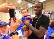 Former Kansas University standout Tyshawn Taylor takes a picture with 9-month-old Takaishi Hartley of Abilene before the annual Rock Chalk Roundball Classic, Thursday, June 13, 2013, at Free State High.
