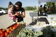 Lawrence resident Torri Nobo and her 20-month-old daughter, Havana, look through a selection of tomatoes from a stand run by Pendleton's Country Market during a farmers market on Wednesday at Clinton Parkway Nursery, 4900 Clinton Parkway.