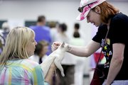 St. Louis resident Kathy Becker holds her Tonkinese cat, Crystal, as Shawnee resident Julie Grindol reaches down to scratch her neck during the Kansas City Midwest Cat Club Show, Saturday June 15, 2013 at the Douglas County Fairgrounds.