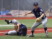 The Raiders' Anthony Miele, left, rolls out of the way while Adam Rea fields the ball and throws to first during the Raiders' game against Midwest Nationals, Sunday at Lawrence High.