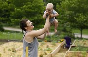 Lawrence resident Nicole Van Walleghem entertains her 10-month-old son, Oren, while her husband, Michael, not pictured, works in their plot at a Common Ground community garden located in the 600 block of Illinois Street earlier this month.