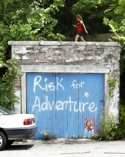 "A pedestrian walks above the old stone garage on Mississippi Street across from Memorial Stadium, which has been repainted with the words ""Risk for Adventure."" For many years the garage, once painted red with the word ""love,"" was a popular backdrop for couples seeking engagement photos."