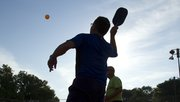 Ron Callaway, 62, reaches into the morning light to hit a pickleball at Lyons Park.