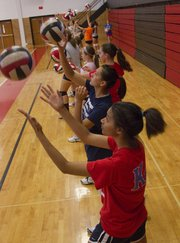 LHS freshman Alexya Davis, 14, works with fellow campers on serving at the LHS volleyball camp on Monday, June 24, 2013, at LHS.