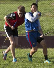 Kansas junior Chris Fellows, Kansas City, Mo., left, tries to wrestle the ball away from senior Hai Nguyen during a quidditch practice Wednesday, April 24, 2013 behind Robinson Gymnasium on the campus of Kansas University.