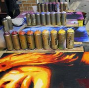 Various colors of spray paint are pictured next to artwork at SeedCo Studios.