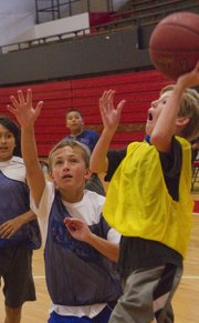Porter Neidow, 11, shoots against Mitchell Spriggs, 11, left, during a summer league basketball game for middle school boys on June 27, 2013, at Lawrence High.