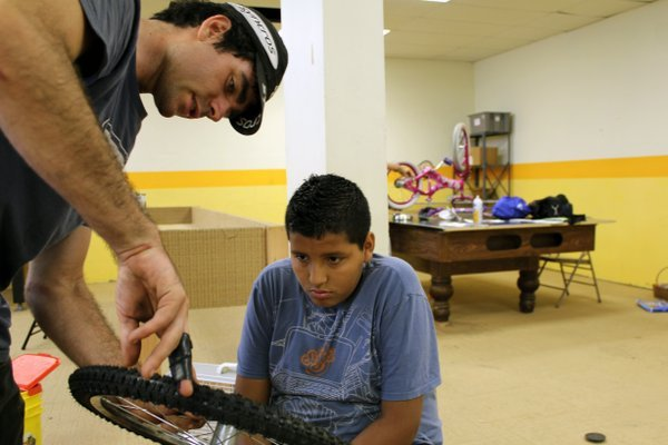 Ben Alexander (left), founder and executive director of FreeWheels for Kids, helped Eduardo Cruz, 12, figure out a tire problem during an Earn a Bike class Wednesday at the Bethel Neighborhood Center in Kansas City, Kan.