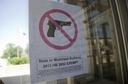 "Mike Yoder/Journal-World Photo.Building maintenance crews for Lawrence and Douglas County have posted new ""no gun"" signs on public buildings, indicating that the local governments have exempted themselves from the state&squot;s new concealed-carry gun law."
