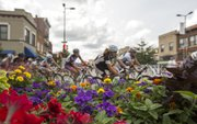A pack of racers race past flowers at the corner of 8th and Massachusetts St. while competing in the women's pro race during the Tour of Lawrence Downtown Criterium races through downtown Lawrence Sunday afternoon.